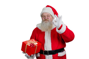 Santa Claus showing ok sign. Studio shot of Santa Claus with Christmas present showing ok gesture on white background.