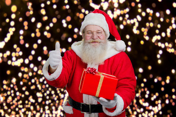 Portrait of cheerful Santa Claus. Happy Santa Claus with red present box giving thumb up gesture on festive lights background. New Year and Santa presents concept.