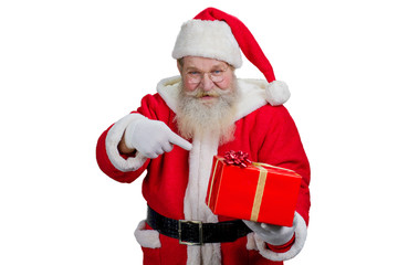 Santa Claus with red gift box. Kind Santa Claus holding Christmas gift and pointing on it with index finger while standing on white background.