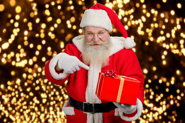 Santa Claus holding beautiful red box. Authentic Santa Claus holding red gift box and pointing on it with his index finger, festive lights background. Happy santa Claus with present box.