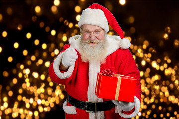 Santa with gift giving thumb up. Happy santa Claus in glasses holding red box with present and gesturing thumb up on New Yewr lights background.