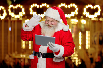 Santa Claus gesturing with pc tablet. Senior santa Claus using digital tablet on festive shimmering background.