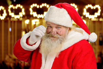 Santa Claus touching his eye glasses. Portrait of kind senior Santa Claus on festive shimmering background close up.