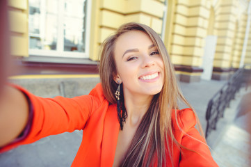 Fashionable look, hot day model of a young woman doing selfie, wearing a red jacket, blond hair outdoors over the city warm background