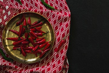 Red chilies in plate on table cloth