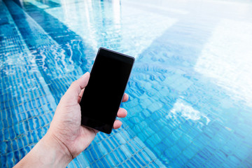 hand  hold smartphone near swiming pool