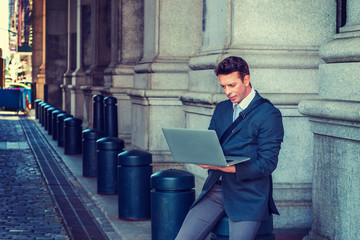 American Businessman traveling, working in New York, wearing striped blazer, carrying shoulder bag, sitting on pillar on street, looking down, reading, working on laptop computer. Instagram effect..