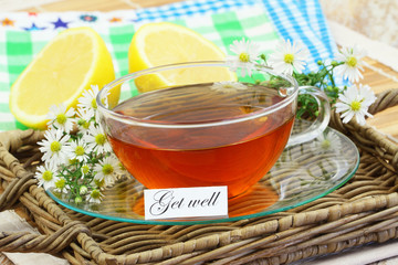 Get well card with cup of chamomile tea, fresh chamomile flowers on wicker tray
