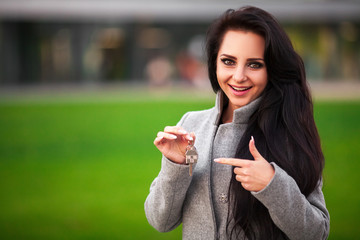 Business, real estate, banking and people concept - smiling business woman with keys over office room or new apartment background