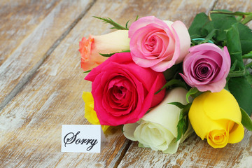 Sorry card with colorful roses bouquet on rustic wooden surface