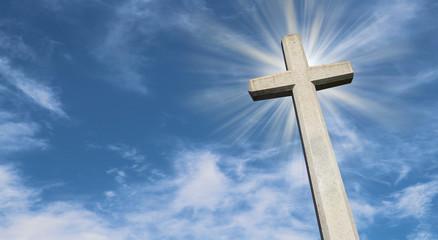 Steinkreuz vor blauem Himmel mit Lichtstrahlen