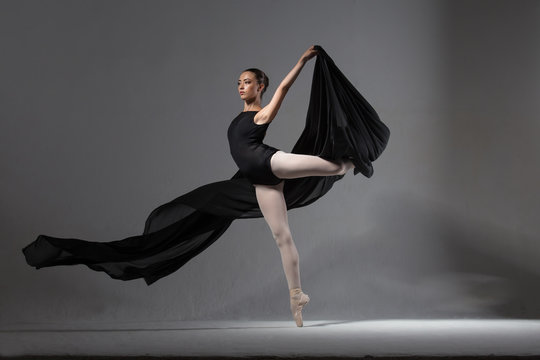 Graceful ballerina in black tights posing with black cloth