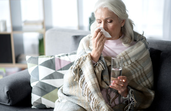 Senior lady suffering from flue at home