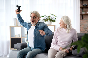Mature married couple playing video game at home