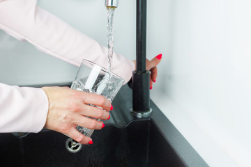 Pouring water into a glass. The woman is tapping the tap water is running water. The glass is filled with water. Thirst, lack of water, global water problem.