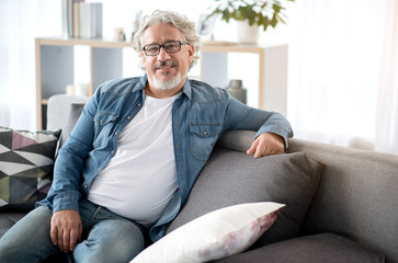Cheerful mature male person relaxing on couch