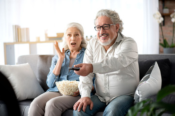 Cheerful mature married couple watching TV together