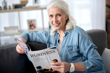 Cheerful mature woman is interested in business news
