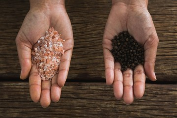 Hands holding sea salt and black pepper seeds