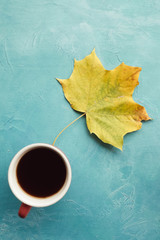 Be warm with black coffee in autumn. Maple leaf on blue background
