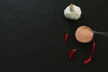 Garlic, red chili pepper and salt on black background