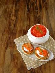 Red caviar in a white ceramic bowl and pancakes with caviar on a wooden table