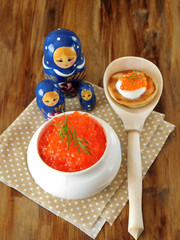 Red caviar in a white ceramic bowl and Russian dolls on a wooden table