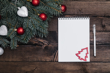 Christmas background with notebook on wood and xmas tree