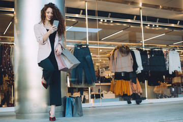 Happy beautiful young redhead woman doing shopping and speaking on the mobile phone