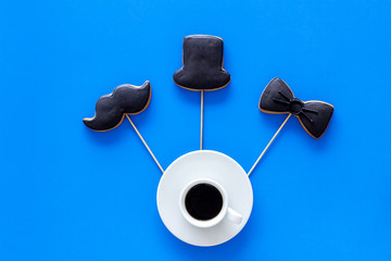 Happy Father's day cards. Black tie, mustache and hat cookies in gift. Blue background top view copyspace