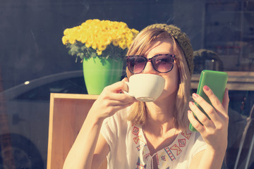 Cute woman drinking coffee and doing a selfie on her cellphone outdoors.