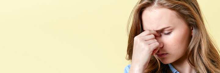 Beautiful teenager girl with ginger hair and freckles having headache and sore eyes. Young woman on yellow background. Tired student.