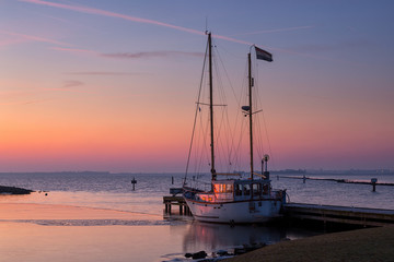 Sail boat at sunrise in the safe harbor