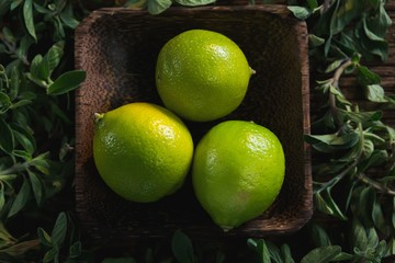 Lime fruits in a bowl with herbs