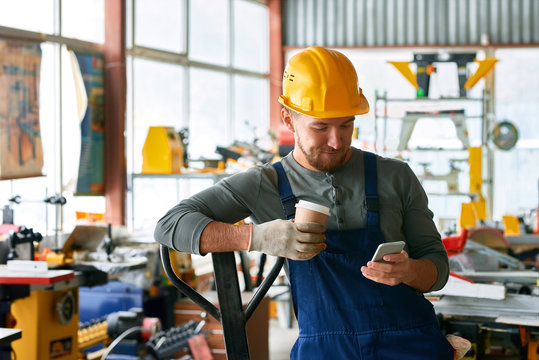 Portrait of young bearded worker taking break in factory workshop: using smartphone and smiling happily holding coffee cup