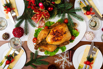 Baked turkey or chicken. The Christmas table is served with a turkey, decorated with bright tinsel and candles. Fried chicken, table. Christmas dinner. Flat lay. Top view