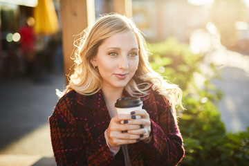 young blond woman with coffee at golden hour