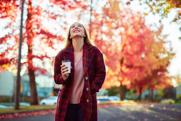 young blond woman with coffee standing under red autumn trees smiling looking up