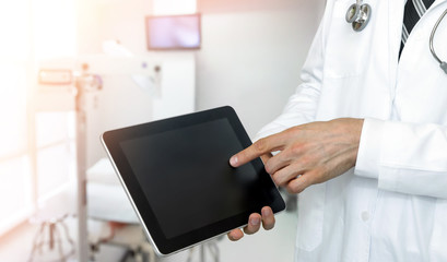 Smart health care internet of things and hospital automation management technology concept with paperless. Doctor with Stethoscope using black display tablet screen for check status of patient.