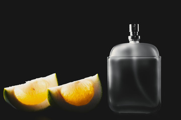 Bottle of modern male perfume and citrus slices on dark background