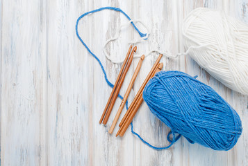 Skeins of yarn and hooks for knitting  on a wooden table.