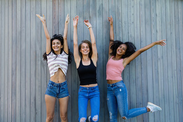 Three best female friends jumping together outdoors near a wall, looking at camera
