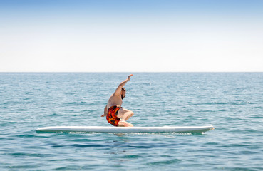 novice surfer beginner falls from the board during training in the sea
