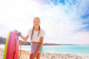 Girl on sandy sunny beach bending over camera