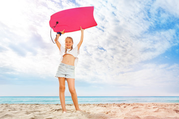 Girl with body board stand on the sunny sand beach