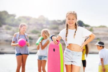 Portrait of cute girl with body board on beach
