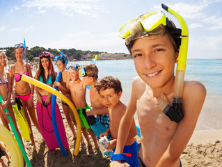 Many kids on beach with boy in snorkeling mask