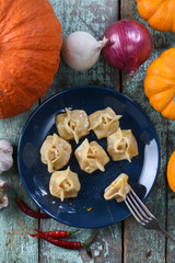 Vegetarian healthy dish. Pumpkin manti, traditional steamed dumplings of Central Asia decorated with raw pumpkins, onions and pepper