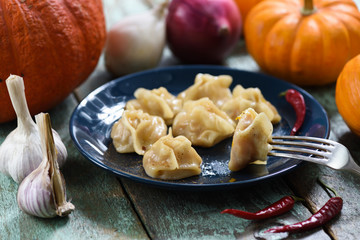 Vegan pumpkin manti, traditional homemade steamed dumplings served with pumpkins, garlic and onions on shabby rustic table