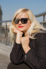 Closeup portrait of blonde model posing in black cloak, wears sunglasses  on a blurred city background